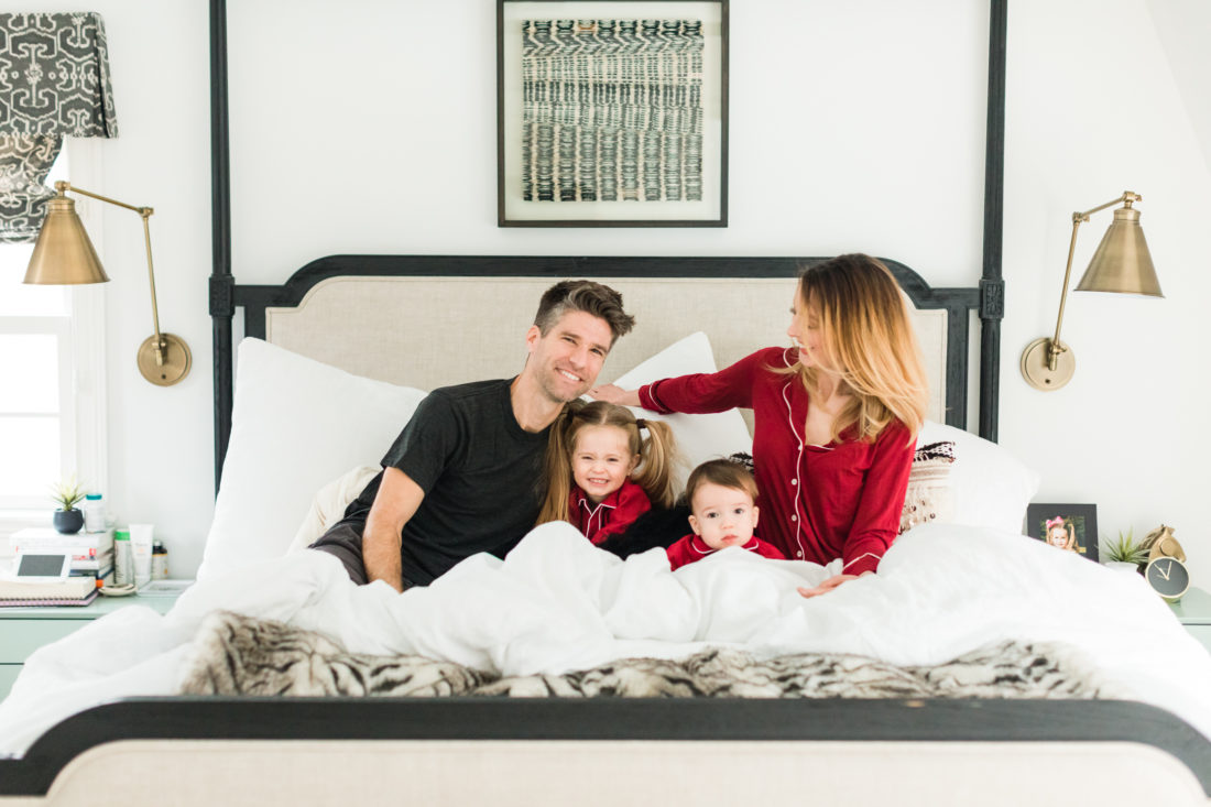 Eva Amurri martino, Kyle Martino, and children Marlowe and Major Martino cuddle in bed wearing red pajamas for Valentine's Day in the master bedroom of their Connecticut home