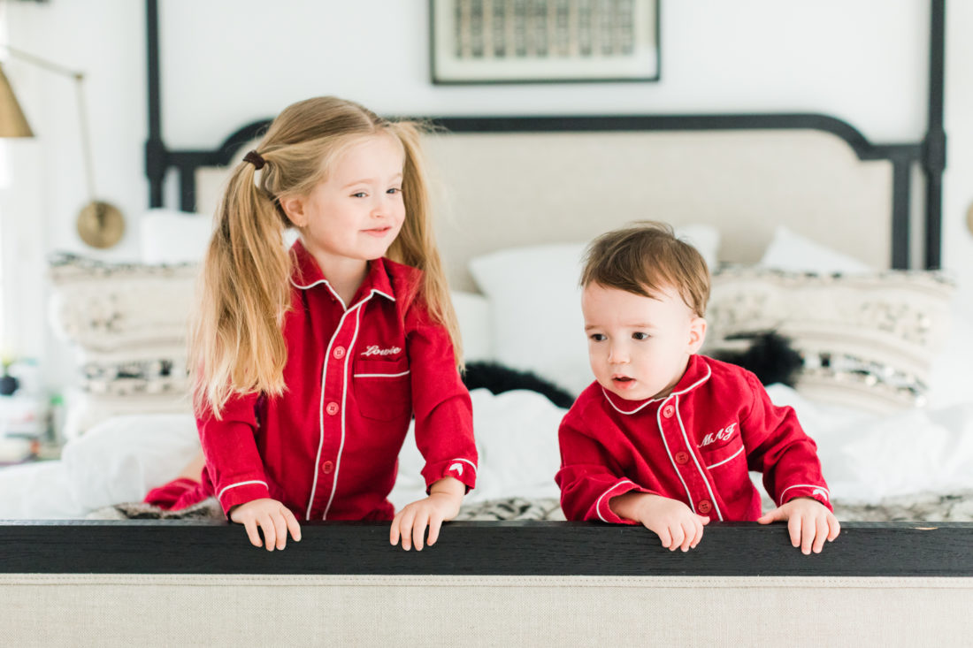 Marlowe and Major Martino kneel at the foot of their parents' bed wearing matching red pajamas for Valentine's Day
