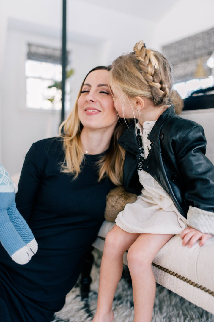 Eva Amurri Martino gets a kiss from her daughter Marlowe Mae, who is wearing an ivory tunic, leather jacket and a halo braid.