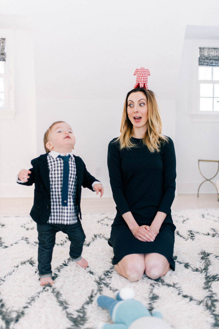 Eva Amurri Martino plays on the rug in her bedroom with son Major James Martino, who is wearing a navy blue blazer, gingham shirt, blue tie and jeans.