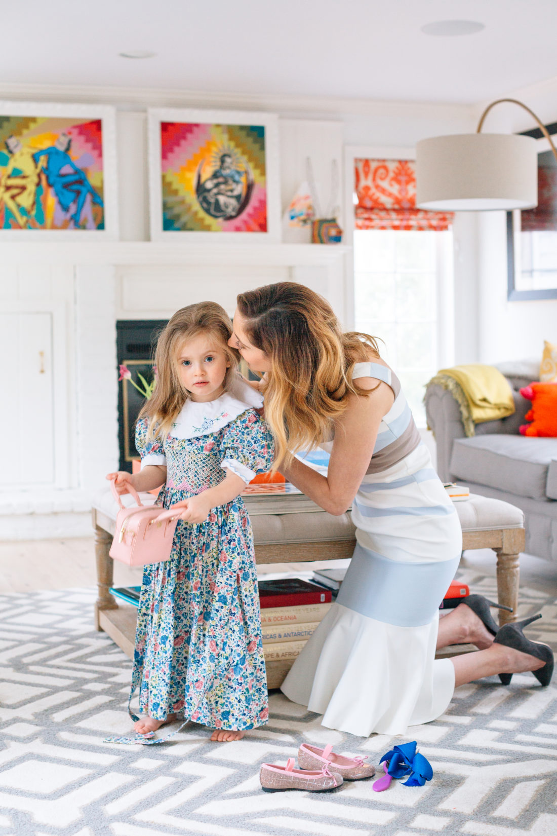 Eva Amurri Martino leans in to whisper in three year old daughter Marlowe's ear as she dresses her in a floral vintage smocked dress for easter and combs through her hair
