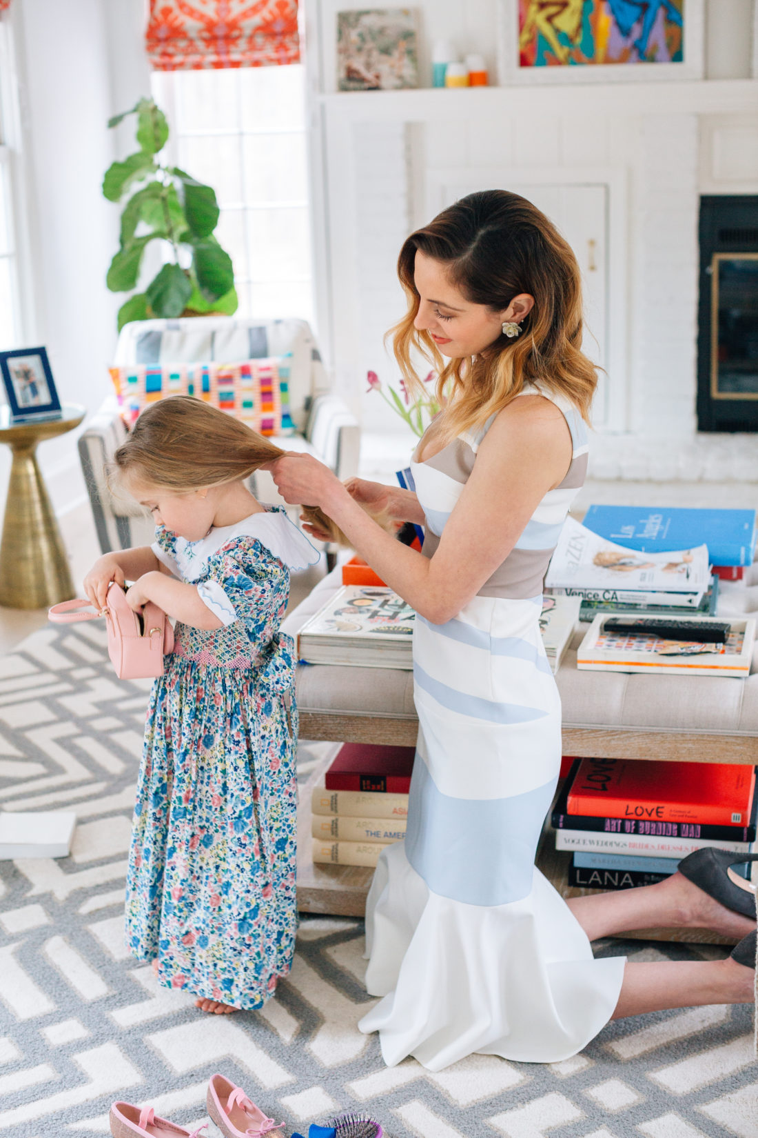 Eva Amurri Martino combs through three year old daughter Marlowe's hair wearing pastel and floral dresses for Easter in the family room of their Connecticut home