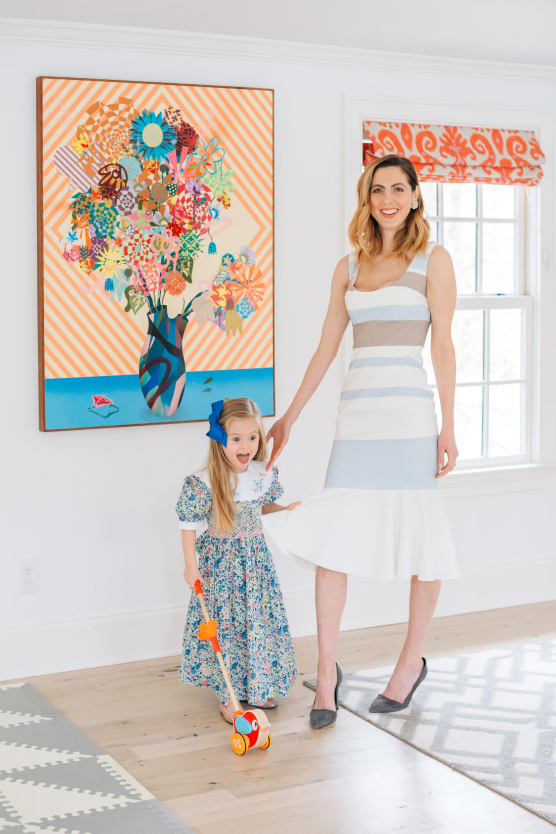 Eva Amurri Martino wears a striped Spring dress and stands with her three year old daughter who wears a floral dress with smocking for Easter