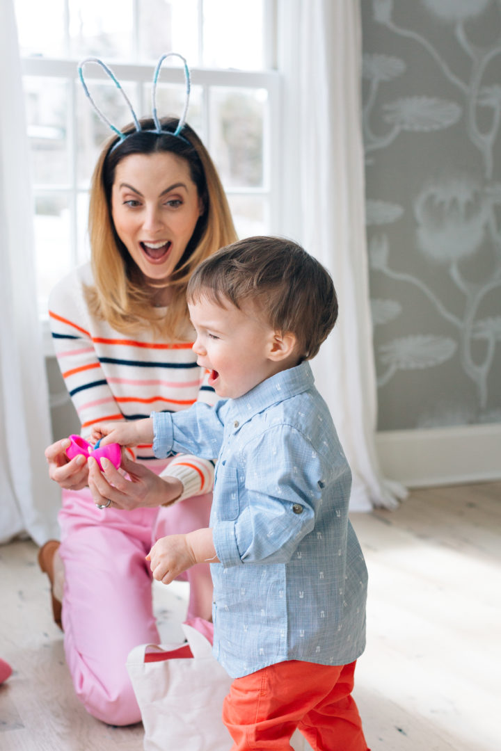 Eva Amurri Martino finding a finger puppet toy inside of a plastic egg during her annual Easter Egg Hunt with her son Major