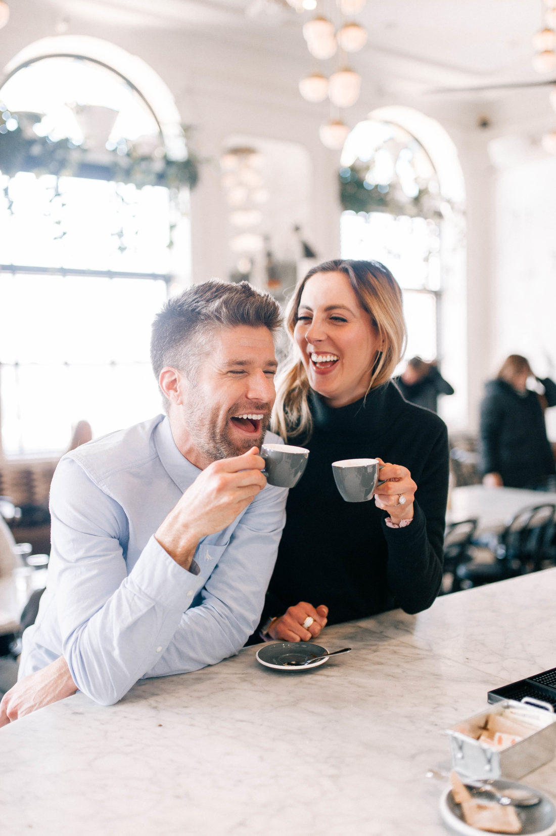 Eva Amurri Martino and Kyle Martino laugh together while drinking espresso at the bar of an NYC restaurant
