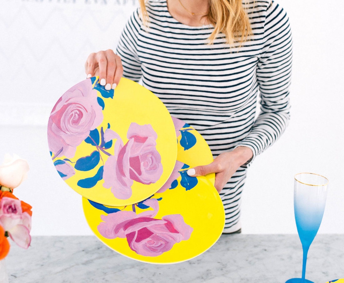 Eva Amurri Martino holds up a set of brightly colored floral melamine plates