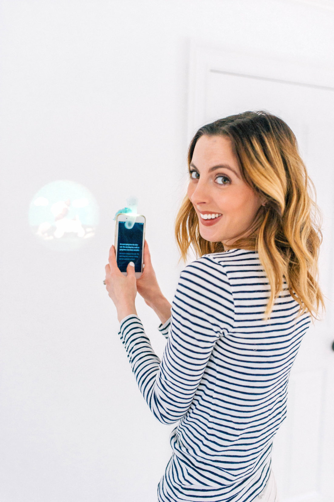 Eva Amurri Martino reads a story and projects images on to the wall with the Moonlite projector and app