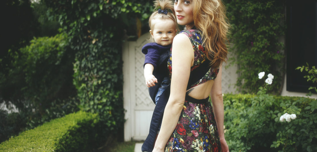 Eva Amurri Martino carrying her daughter Marlowe in a carrier with a suitcase ready to travel