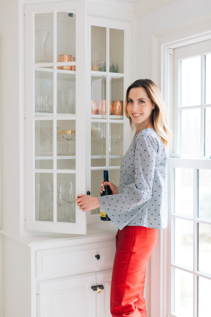 Eva Amurri Martino grabs a bottle of red wine in a blue top at her Connecticut home
