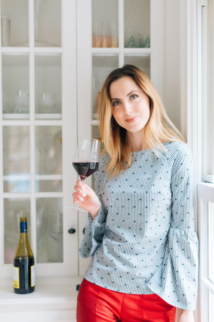 Eva Amurri Martino sips on a glass of red wine in a blue top at her Connecticut home