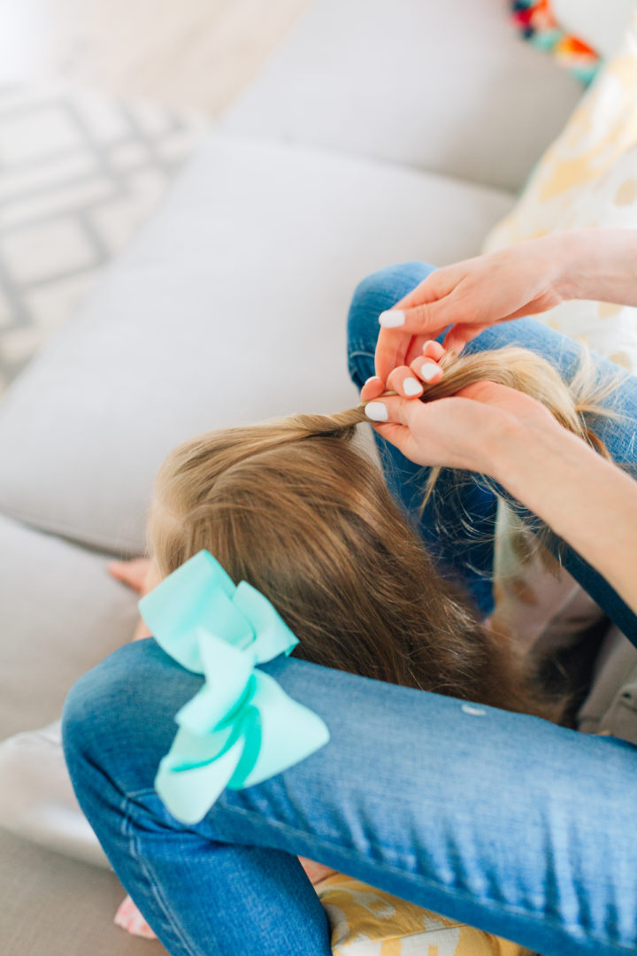 Eva Amurri Martino styles her daughter Marlowe's hair while she sits on the couch with a blue bow hairtie on her knee.