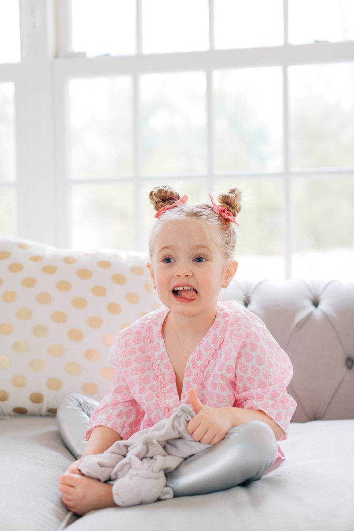 Marlowe Martino shows off her twisted double bun hairstyle on the couch in her Connecticut home.