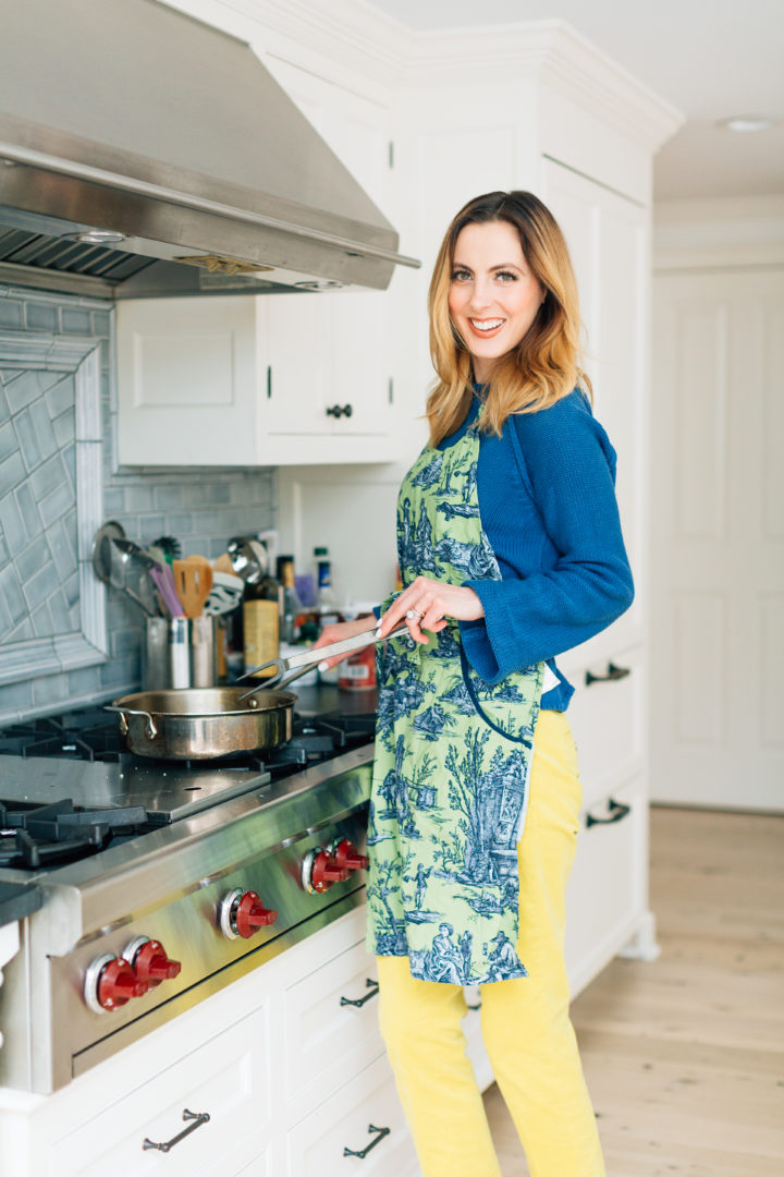 Eva Amurri Martino in a green apron cooking Chicken Milanese
