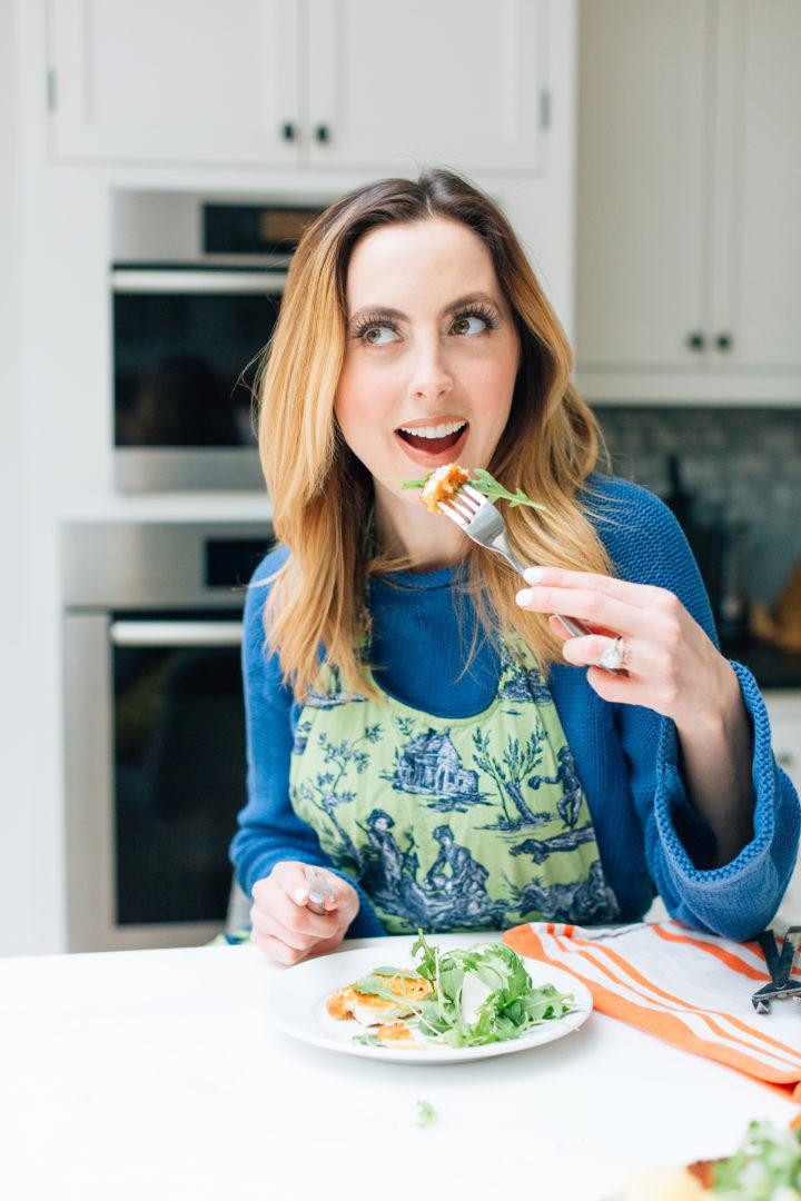 Eva Amurri Martino in a green apron eating Chicken Milanese