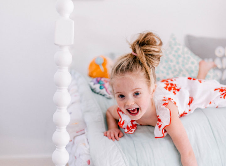 Eva Amurri Martino's daughter Marlowe lies on her bed in a topknot a bright dress