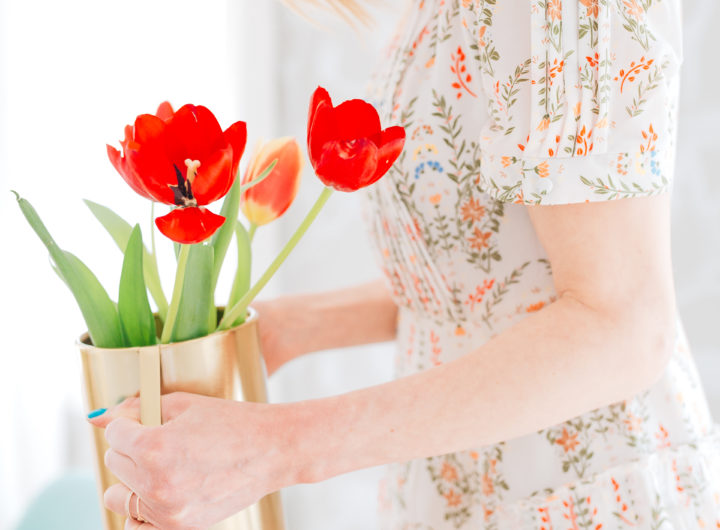 Eva Amurri Martino wears a vintage-inspired dress holding a gold vase full of red tulips
