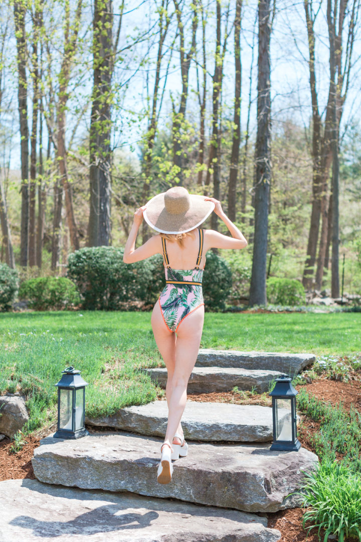 Eva Amurri Martino wears a jungle inspired one piece bathing suit and a large brim hat by her pool in Connecticut