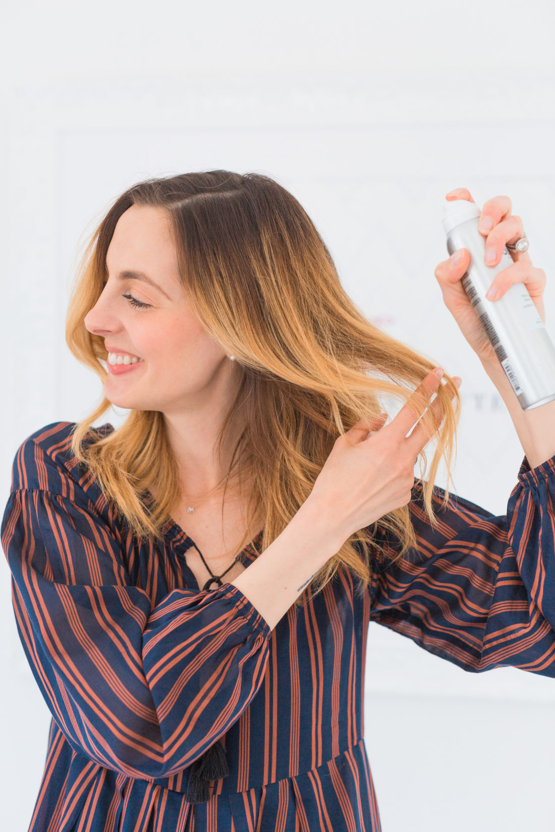 Eva Amurri Martino sprays some texturizing hairspray in to her freshly styled hair