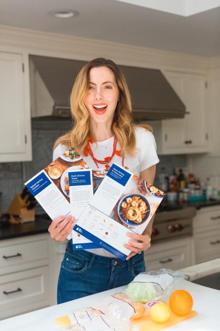 Eva Amurri Martino holds up Blue Apron meal plan recipes sheets.