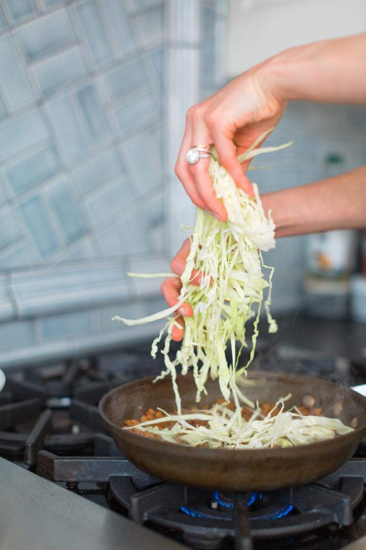 Eva Amurri Martino shreds lettuce in a skillet.