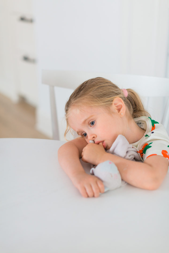 Eva Amurri Martino's daughter Marlowe sucks her thumb and rests her head on the table