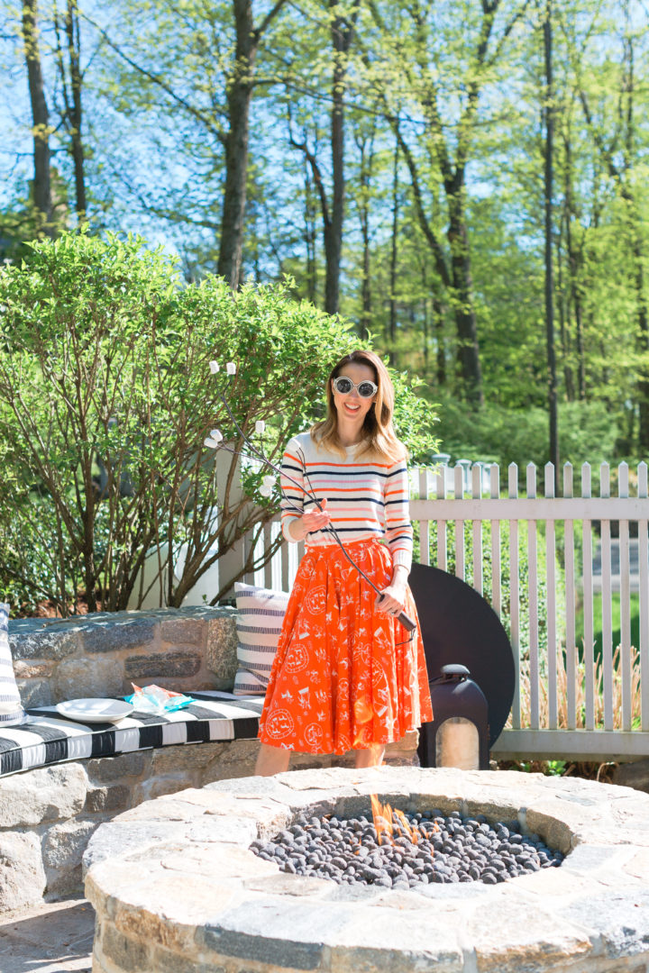 roasts marshmallows in a colorful frock at her Connecticut home