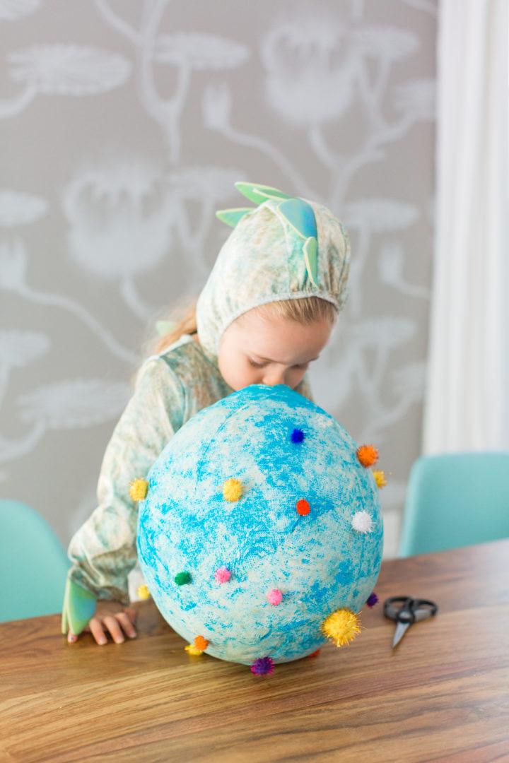 Eva Amurri Martino's daughter Marlowe wears a dinosaur costume and plays with a paper mache dinosaur egg