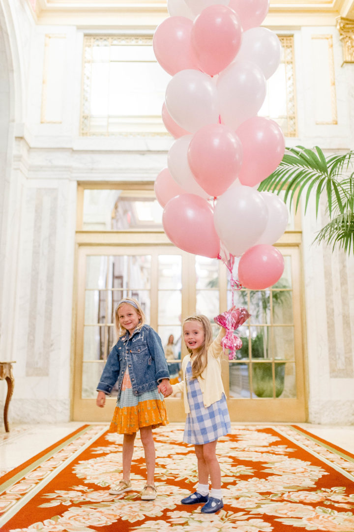 Eva Amurri Martino's daughter Marlowe carries pink and white balloons while walking through the iconic Plaza Hotel with a friend