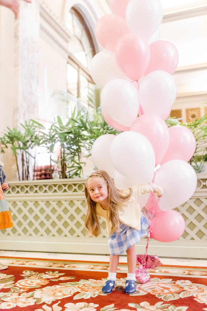 Eva Amurri Martino's daughter Marlowe carries pink and white balloons while walking through the iconic Plaza Hotel