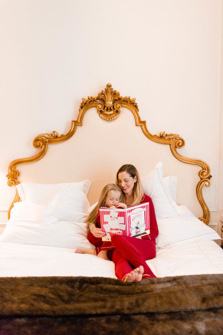 Eva Amurri Martino reads Eloise to her daughter Marlowe on a bed at the Plaza Hotel in New York City