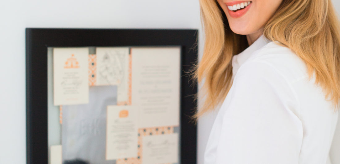 Eva Amurri Martino displays a frame with her wedding invitations on her wall