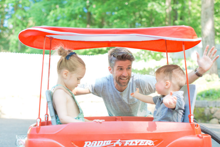 Kyle Martino laughs with his kids Marlowe and Major in a wagon.
