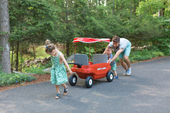 Marlowe Martino pulls a red wagon in her driveway while brother Major and dad Kyle push from behind.