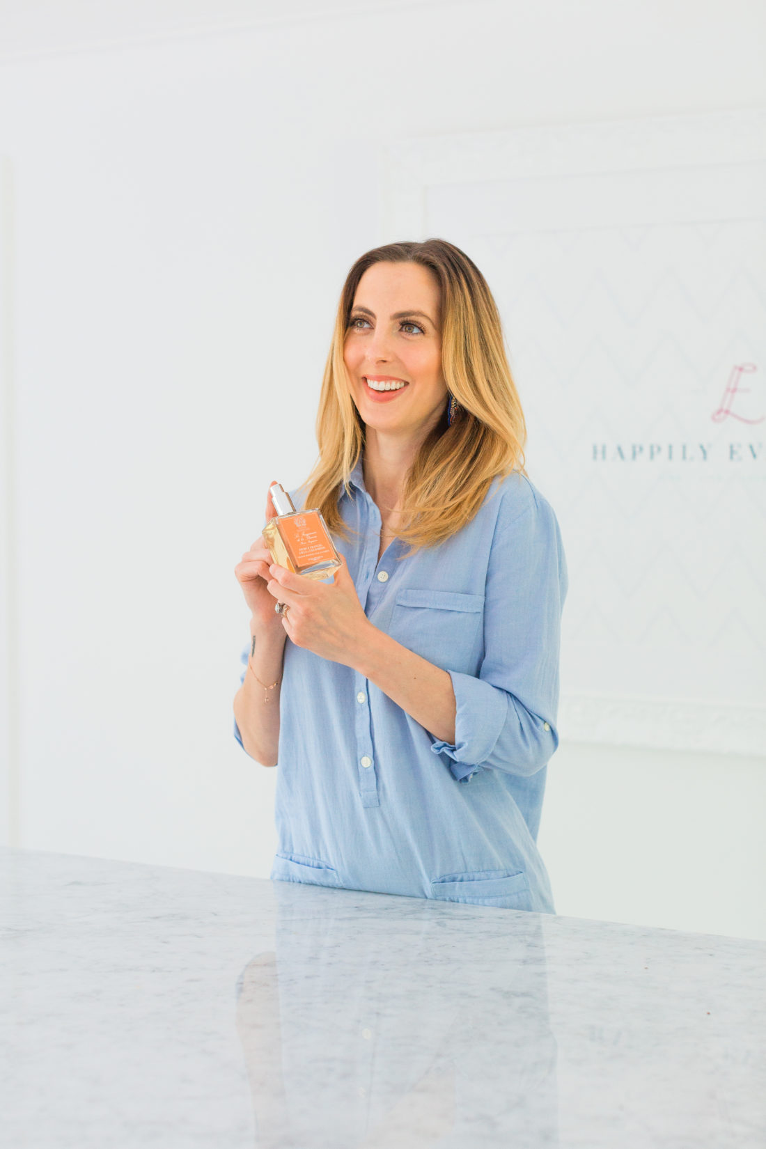 Eva Amurri Martino wears a light blue shirt dress and holds a bottle of Antica Farmacista room spray