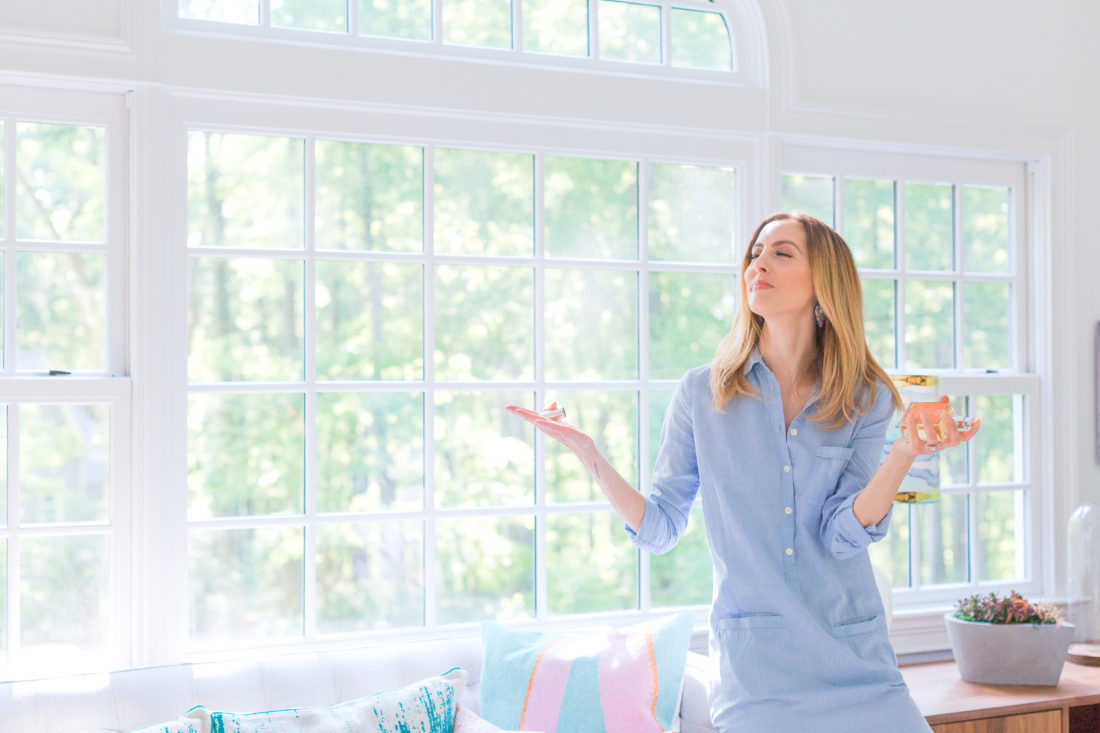 Eva Amurri Martino wears a light blue shirtdress and sprays Antica Farmacista room spray in her studio