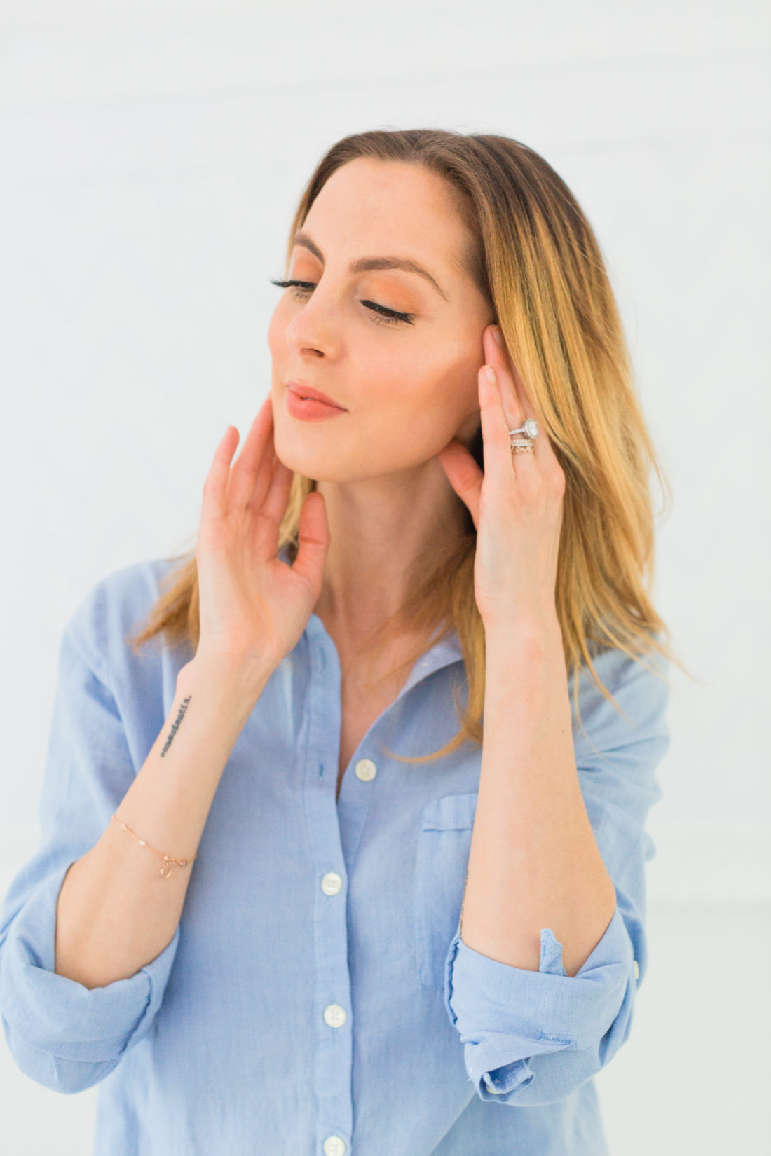 Eva Amurri Martino wears a light blue shirtdress and blends in her foundation for a flawless and glowing makeup look