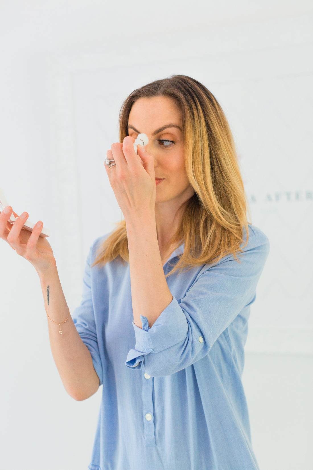 Eva Amurri Martino wears a light blue shirtdress and applies Fenty Beauty blotting powder to her face