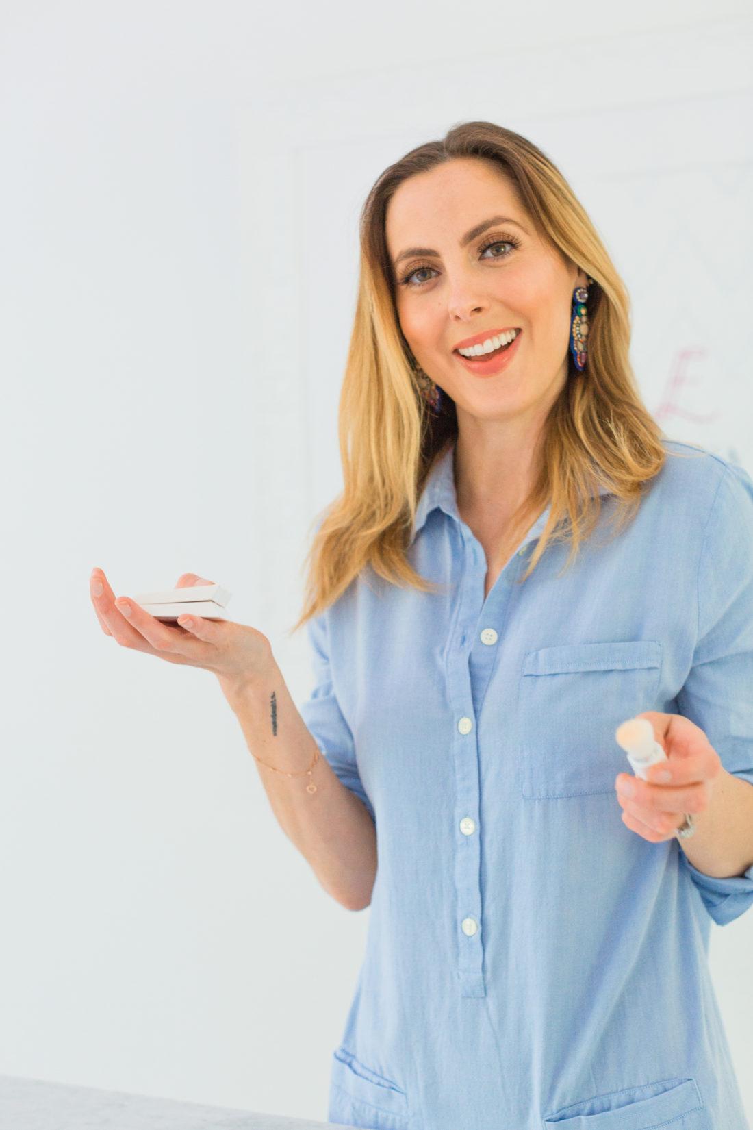 Eva Amurri Martino wears a light blue shirtdress and applies Fenty Beauty blotting powder to her face