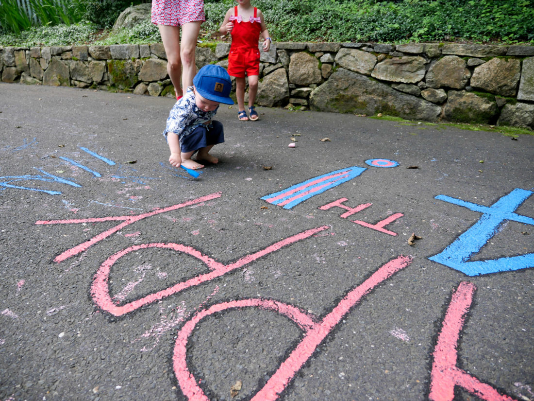 Major Martino paints with chalk paint in the driveway of his Connecticut home on the fourth of july