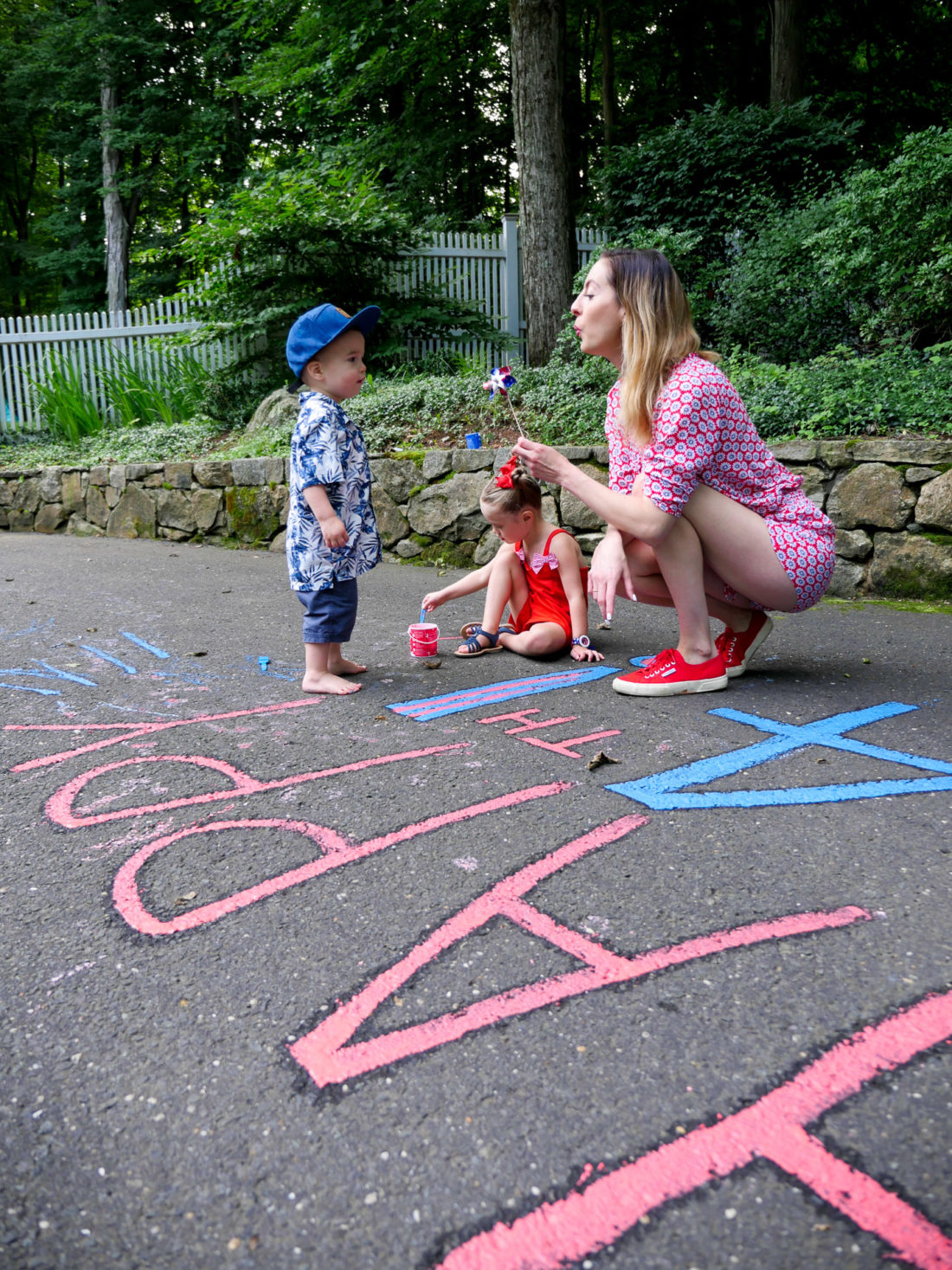 Eva Amurri Martino wears a red white and blue romper, and blows on a pinwheel on the fourth of july at home in Connecticut