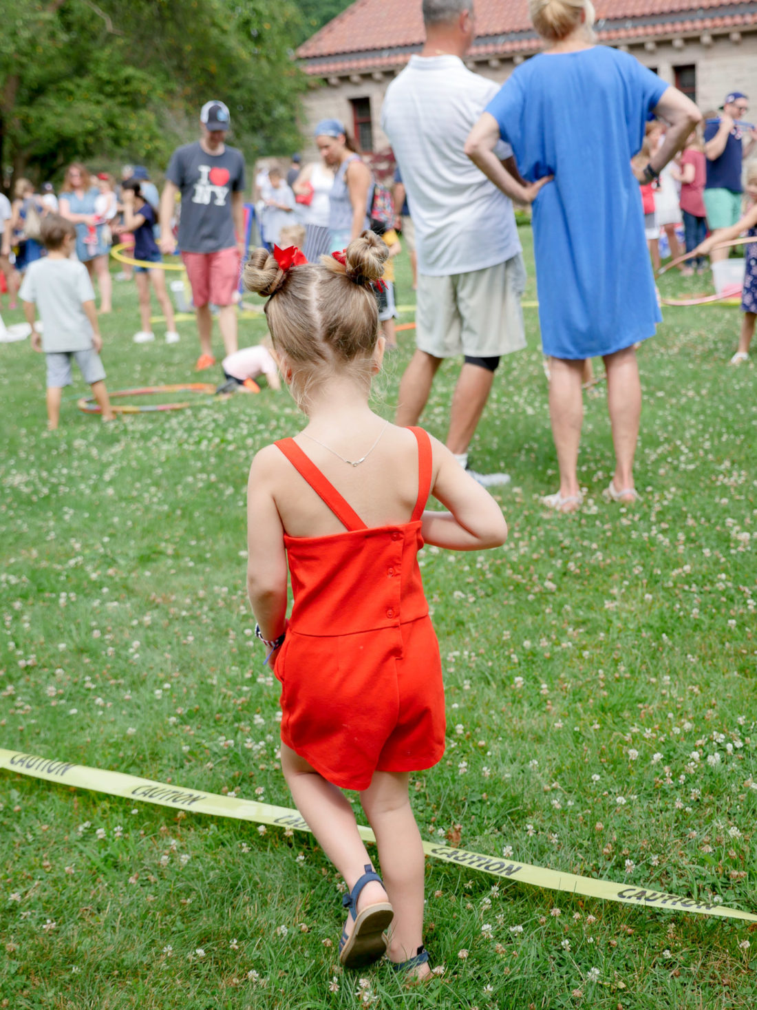 Marlowe Martino wears a red romper and explores a fourth of july lawn party