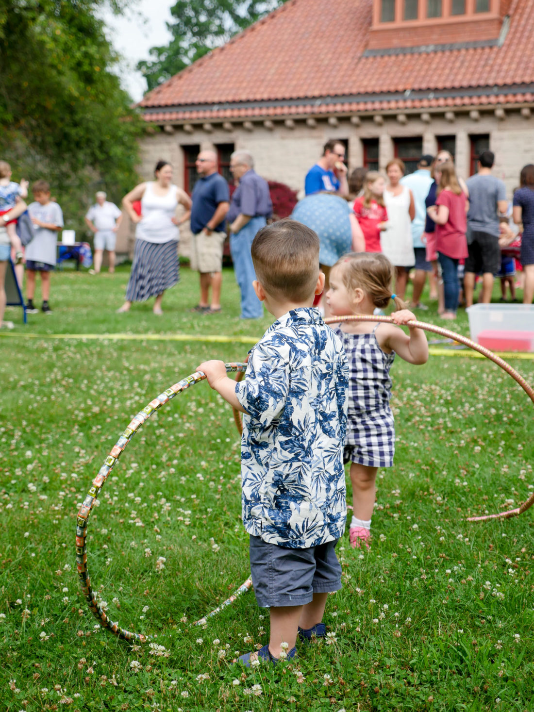 Major Martino wears a white and blue hawaiian shirt and plays with a hula hoop at a fourth of july lawn party