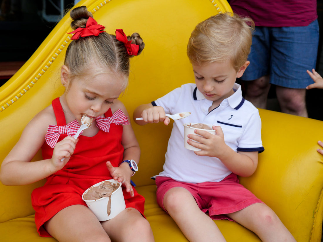 Marlowe Martino wears a red romper and eats ice cream with a friend on the fourth of july