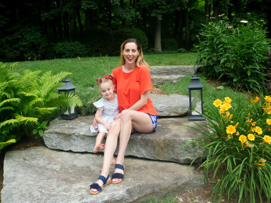 Eva Amurri Martino wears a red top and patterned blue and white shorts, and sits on the steps in her backyard on the fourth of july