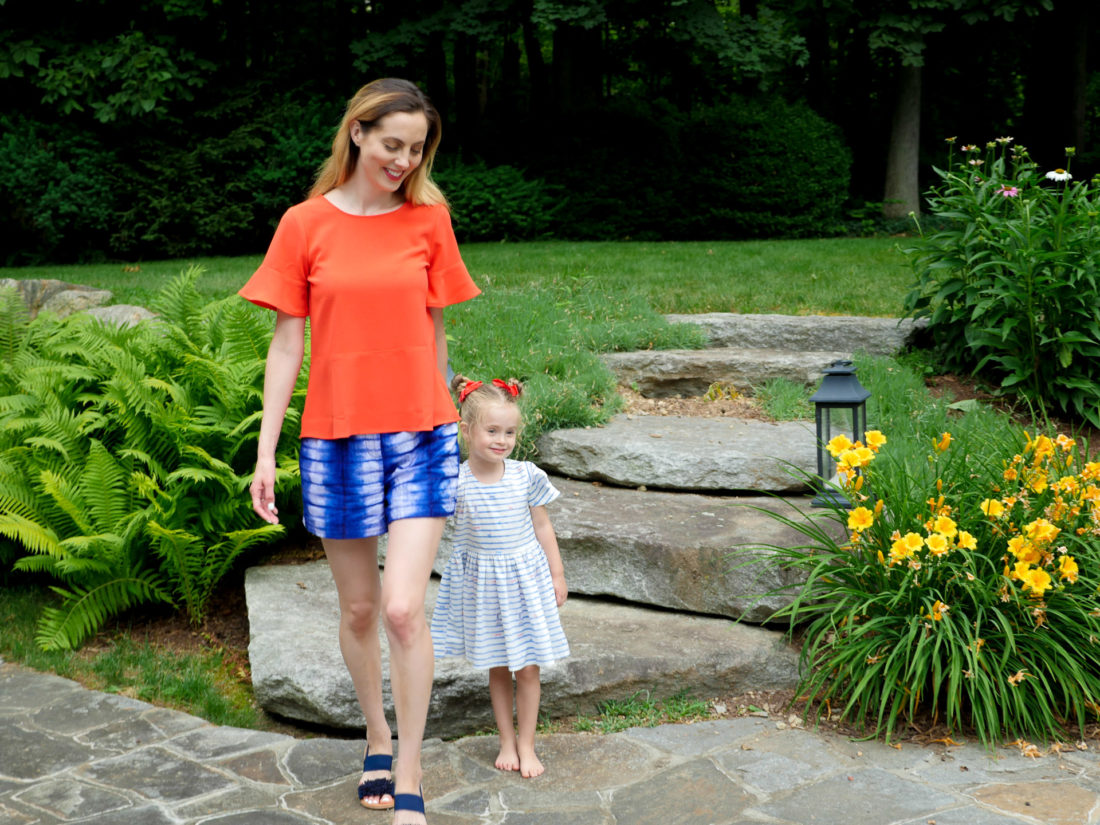 Eva and Marlowe Martino walk through their backyard wearing red white and blue on the fourth of july
