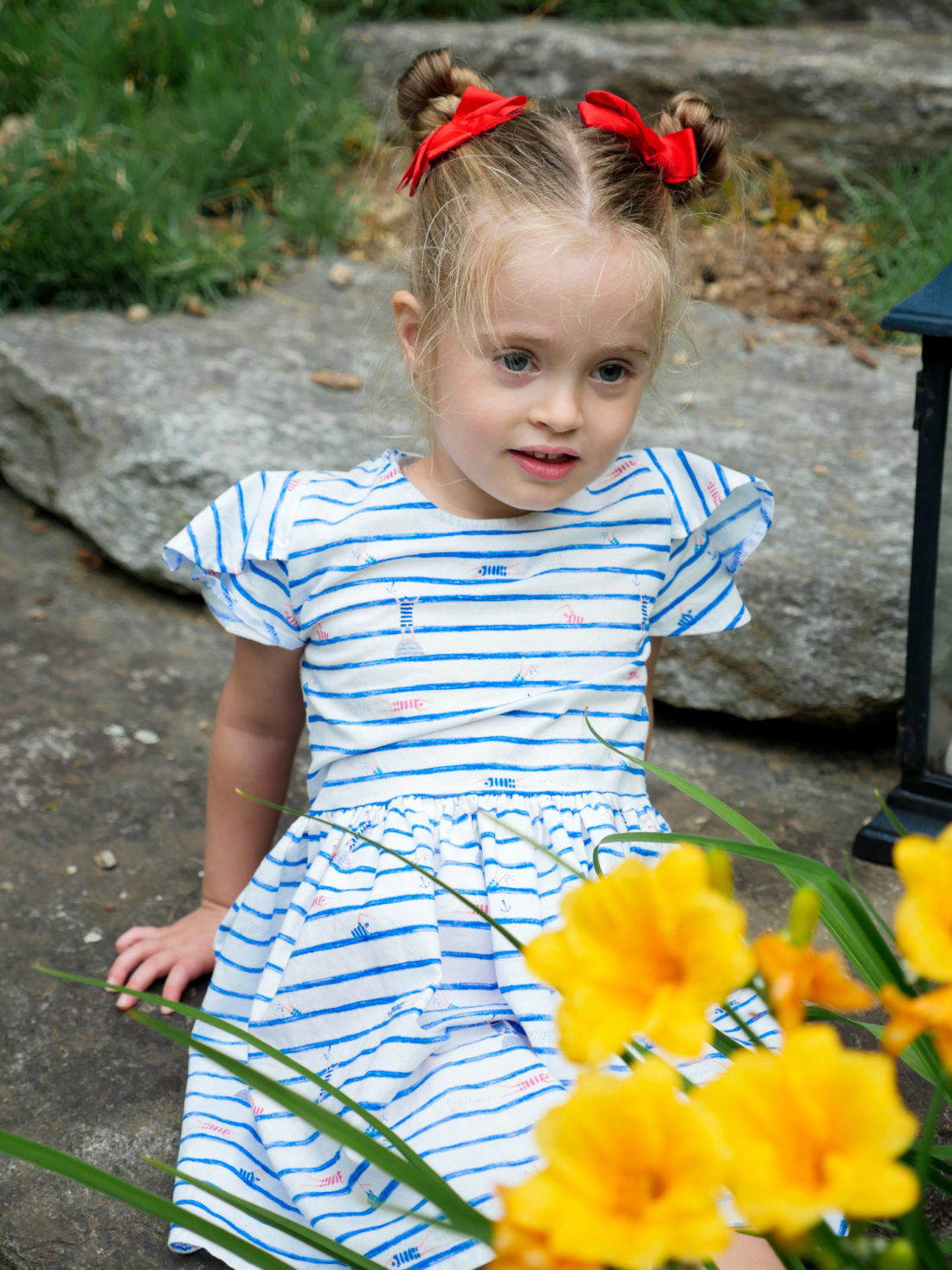 Marlowe Martino sits beside some daffodils wearing a red white and blue dress on the fourth of july