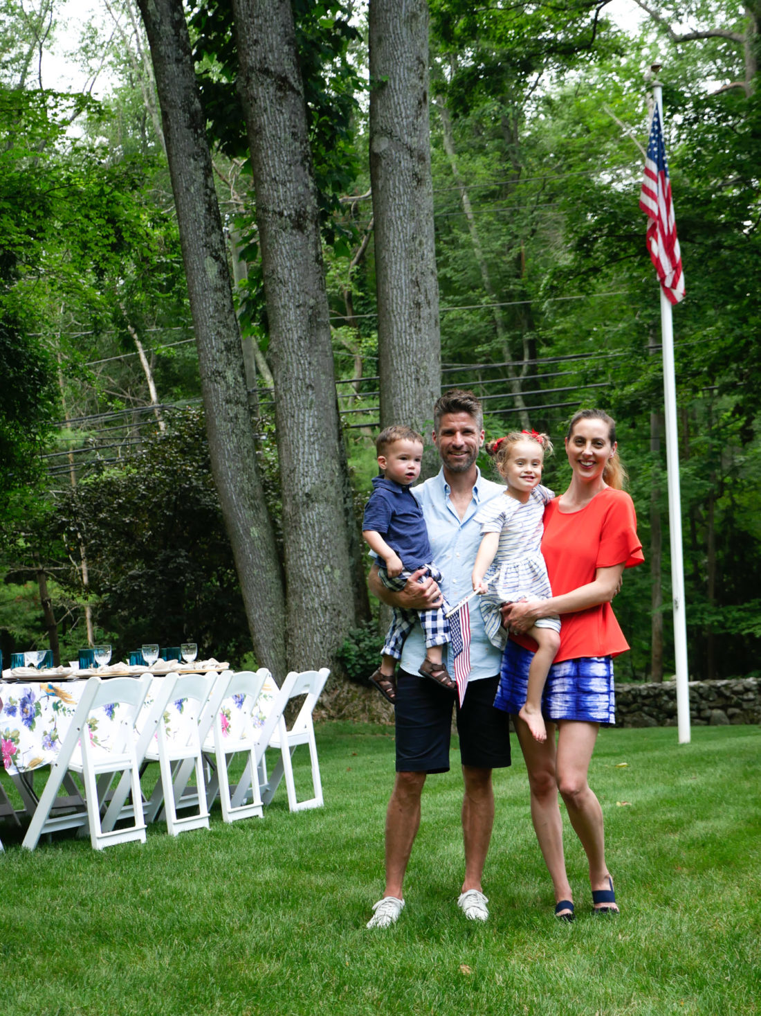EvaAmurri Martino, Kyle Martino, Marlowe Martino, and Major Martino post together at a family fourth of july party wearing red white and blue