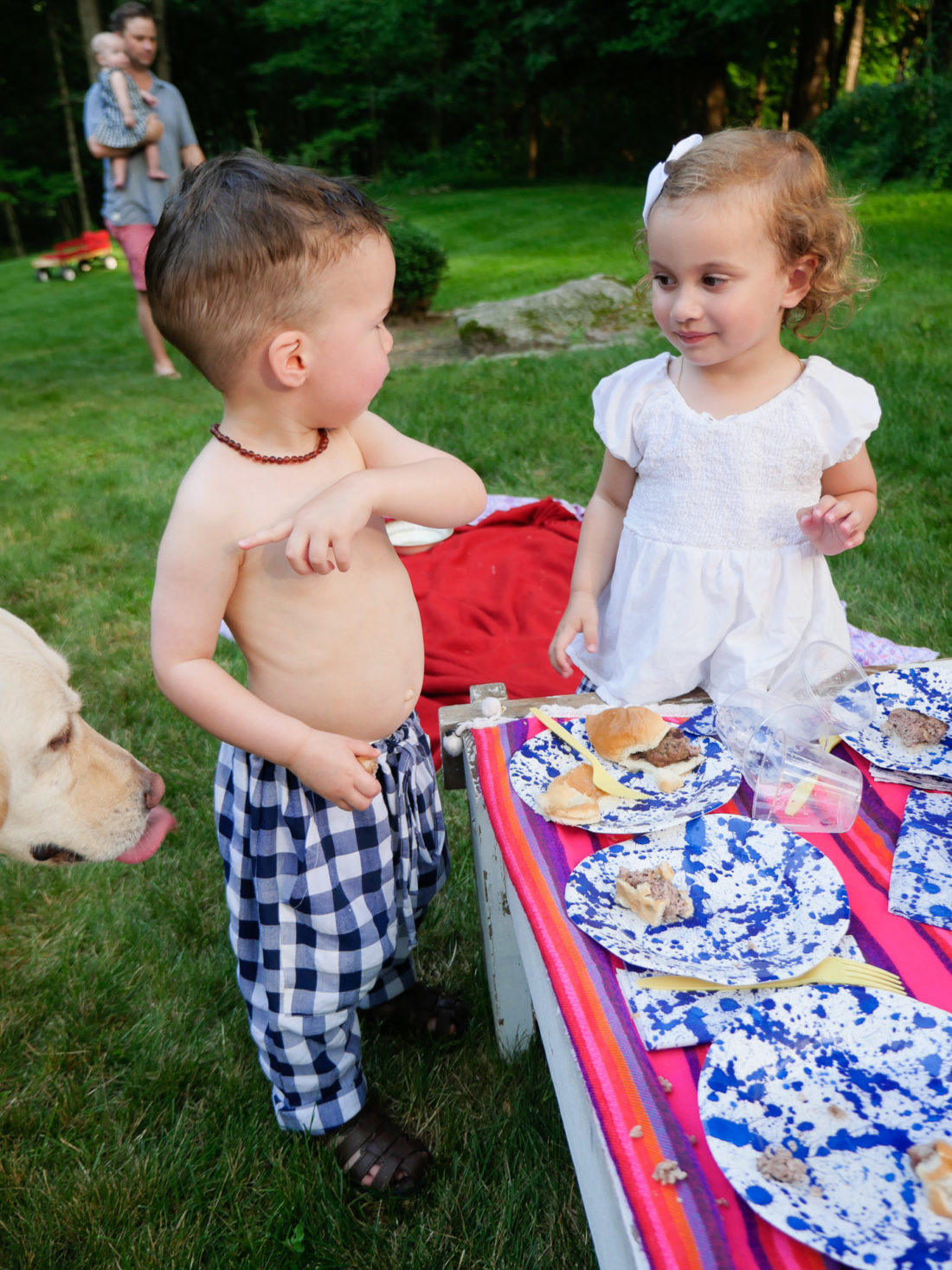 Major Martino wears white and blue checked pants and stands with a little girl on the fourth of july in Connecticut