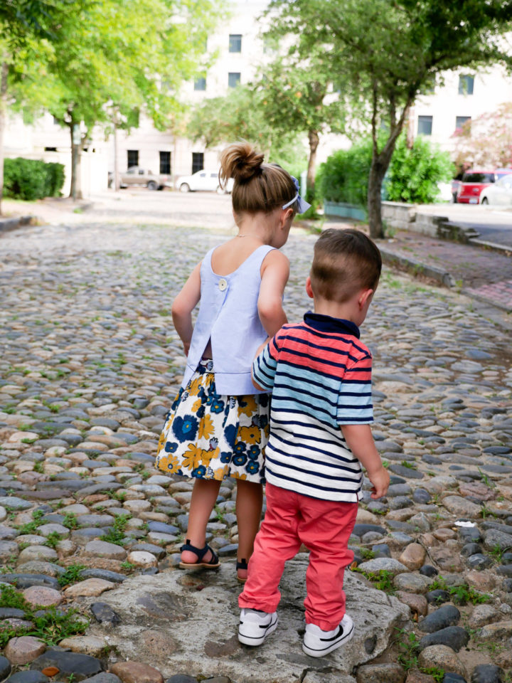 Eva Amurri Martino's kids Marlowe and Major hold hands on a cobblestone street in Charleston