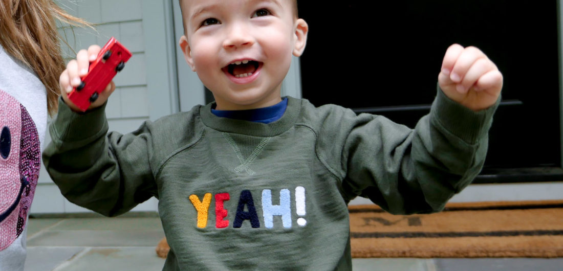 Eva Amurri Martino's son Major throws his hands in the air wearing a 'yeah!' sweatshirt